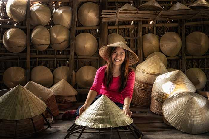 female craftsman making the traditional vietnam hat in the old traditional house in Ap Thoi Phuoc village, Hochiminh city, Vietnam